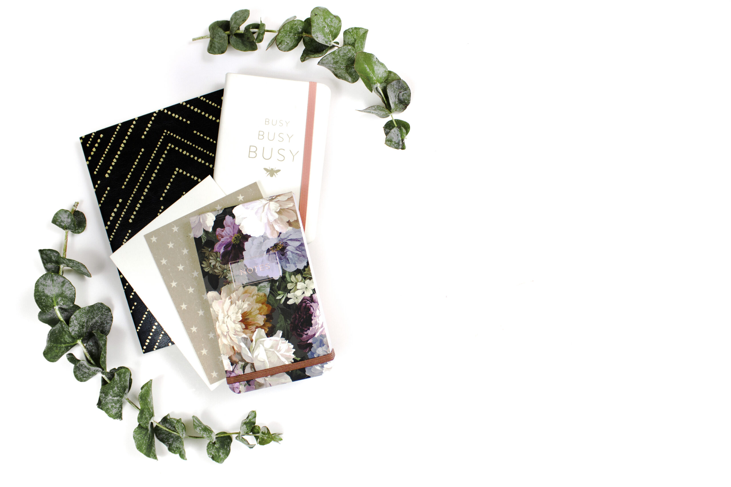 Flatlay photograph featuring pile of notebooks and leaves surrounding.